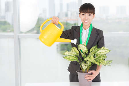 Portrait of a woman watering a plant with a watering-pot inside Stock Photo