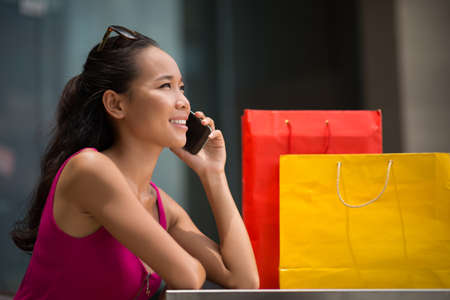 or spree: Lovely girl using a mobile phone in the shopping mall