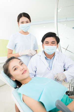 dentalcare: Vertical portrait of a female patient and two professional dentists