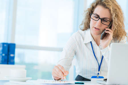 Professional consultant speaking with her client on the phone
