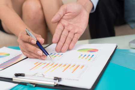 Business people analyzing financial statistics as a part of the annual report Stock Photo
