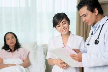 Talking doctor and nurse on the foreground Stock Photo