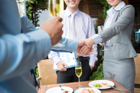business partners: Image of businesspeople handshaking after signing a contract during a lunch Stock Photo