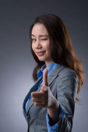 Vertical portrait of a squinting young businesswoman pointing at you