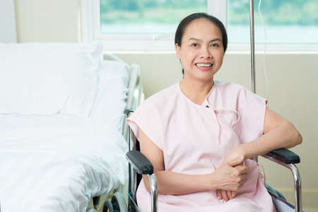 Portrait of a smiling female patient looking at camera and sitting in the wheel-chair