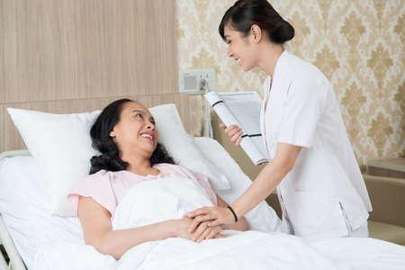 Beeld van een patiënt en een verpleegster die in de het ziekenhuiskamer spreken