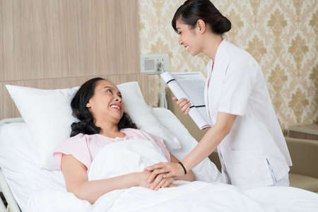 Image of a patient and a nurse talking in the hospital chamber Stock Photo