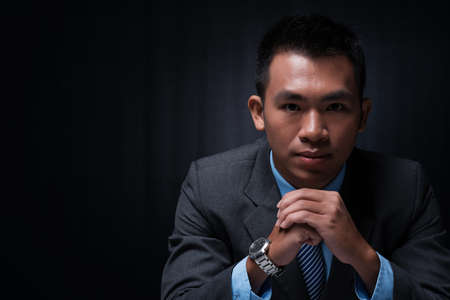 over black: Copy-spaced portrait of a young businessman thinking over the business strategy over a black background Stock Photo