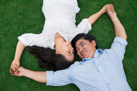 Angle view of a happy senior couple lying on the grass