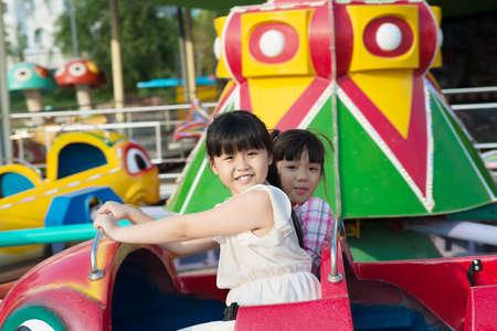 Portrait of pretty little girls taking an amusement ride Stock Photo