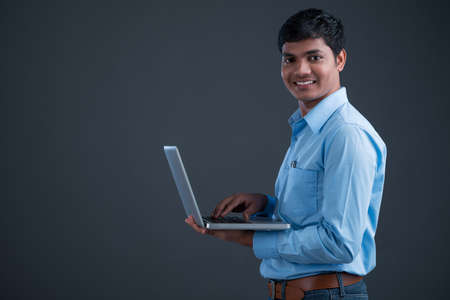 experienced operator: Isolated portrait of a smiling businessman holding a portable device Stock Photo