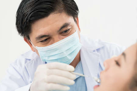 dentalcare: Close-up image of an experienced dentist examining a patient