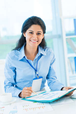 financial reports: Vertical portrait of a young business lady reviewing financial reports