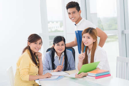 Group portrait of three diligent students and their experienced teacher