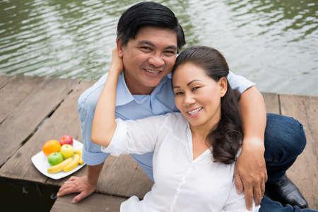 romantics: Close-up portrait of a happy mature couple resting on the riverside