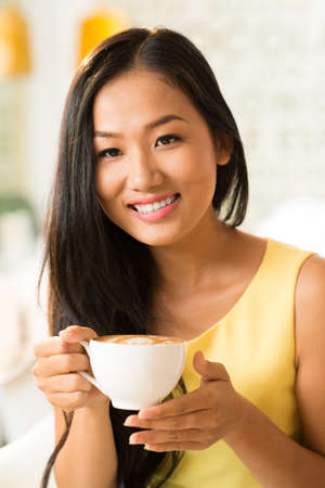 Close-up portrait of a lovely female coffee addict drinking latte at a cafeteria