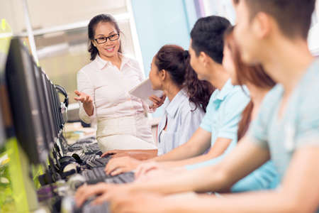 asian group: Image of a high school teacher teaching in the computer classroom on the foreground