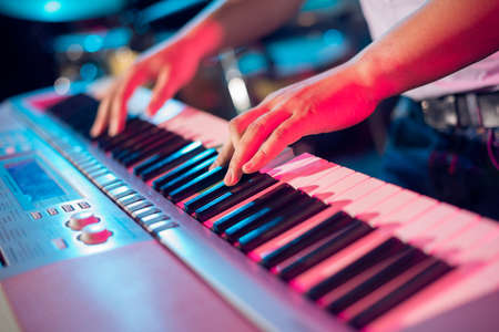 Human hands playing the piano on the party
