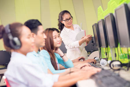 Image of students sitting in the computer class during the lesson with their teacher on the foreground