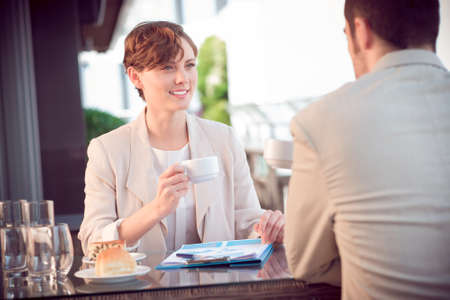 lovely businesswoman: Image of a lovely businesswoman with a teacup on a business lunch with her partner on the foreground  Stock Photo
