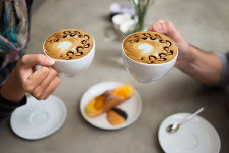 cups of coffee: Cropped image of a couple drinking latte coffee in the coffee shop on the foreground Stock Photo