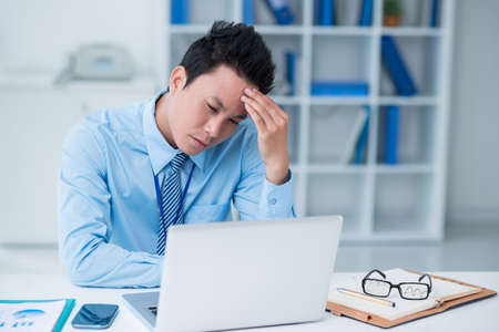 overwork: Copy-spaced image of a tired businessman sitting at the office Stock Photo