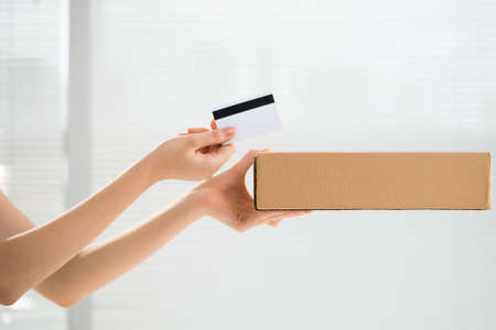 Cropped image of human hands holding a parcel and a credit card