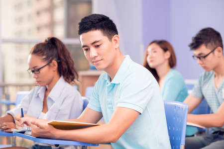 Image of a young student doing the test sitting on the foreground Stock Photo