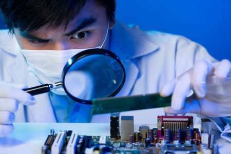 technician: An electronic engineer analyzing the computer motherboard with the zoom on the foreground
