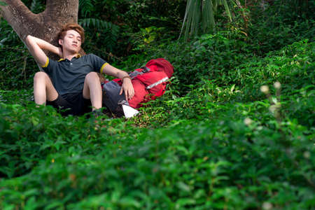 eyesclosed: A young tired tourist napping in the forest on the foreground