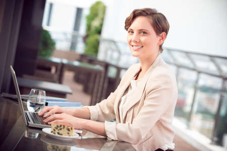 lovely businesswoman: Portrait of a lovely businesswoman typing and posing at camera