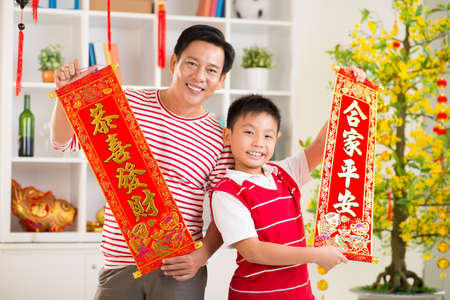 vietnamese ethnicity: �lose up portrait of a father and his son holding red textiles with greetings for the New Year on the foreground