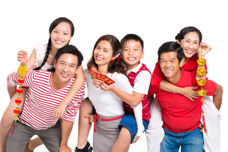 Close up portrait of a cheerful family having fun with Tet decorations isolated on white Stock Photo