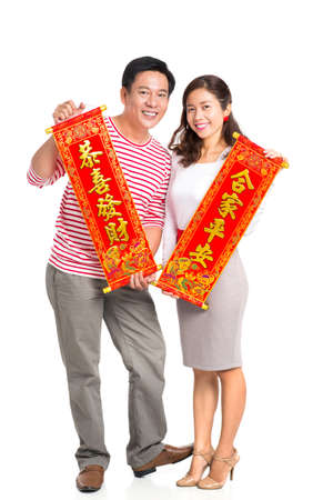 Vertical portrait of a married couple holding red textiles with Tet greetings over a white background