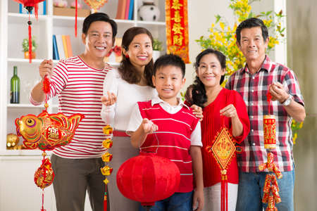 Close up portrait of a big Asian family showing Tet symbols with traditional greetings at home
