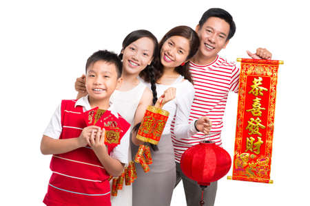 Portrait of a friendly Asian family wishing happiness in the New Chinese Year standing against a white background