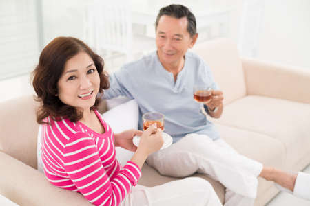 Senior man and woman sitting comfortably and enjoying their weekend at home Stock Photo