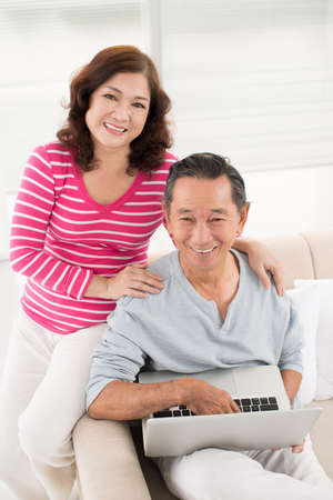 old asian: Vertical portrait of modern retirees having no trouble using a laptop