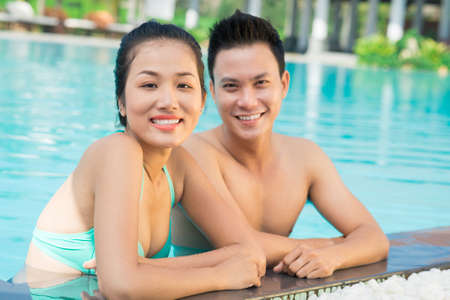 Close up portrait of a young couple in the swimming pool on the foreground