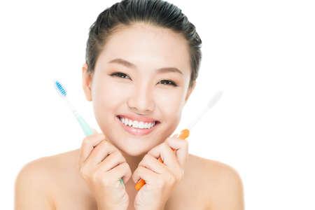 dentalcare: Isolated image of a joyful girl choosing between two toothbrushes