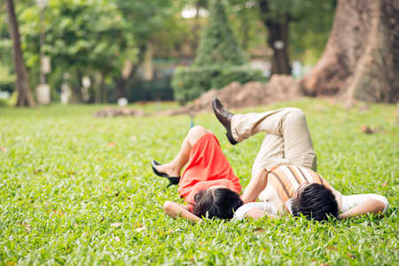 Copy-spaced image of a happy senior couple lying on the green grass in the park on the foreground