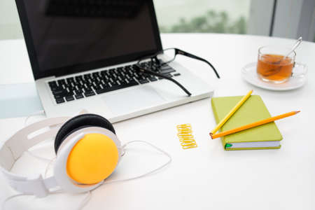 Close-up image of a workplace with colorful office supplies and headphones Stock Photo