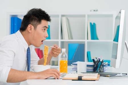 직장에서 국수와 함께 점심을 먹는 사무실 사람의 재미 있은 쐈어. 스톡 콘텐츠