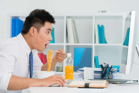 Funny shot of an office guy lunching with noodles on the job 版權商用圖片