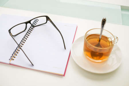 personal organiser: Close-up image of a morning workplace at office with a copybook and a cup of tea