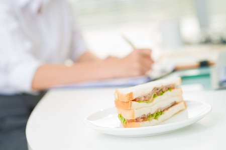 Close-shot of an appetizing sandwich on the plate in office Stock Photo