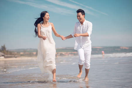 Image of a young couple running on a sandy beach