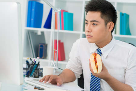 Busy office guy eating a hot-dog instead of a proper lunch Фото со стока