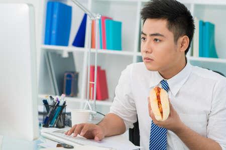Chico de la oficina ocupada comiendo un hot-dog en lugar de un almuerzo adecuado Foto de archivo