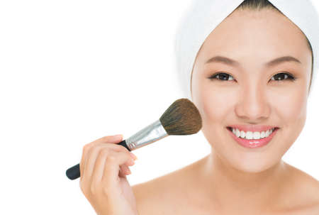 Portrait of a girl applying blusher on her cheeks Stock Photo